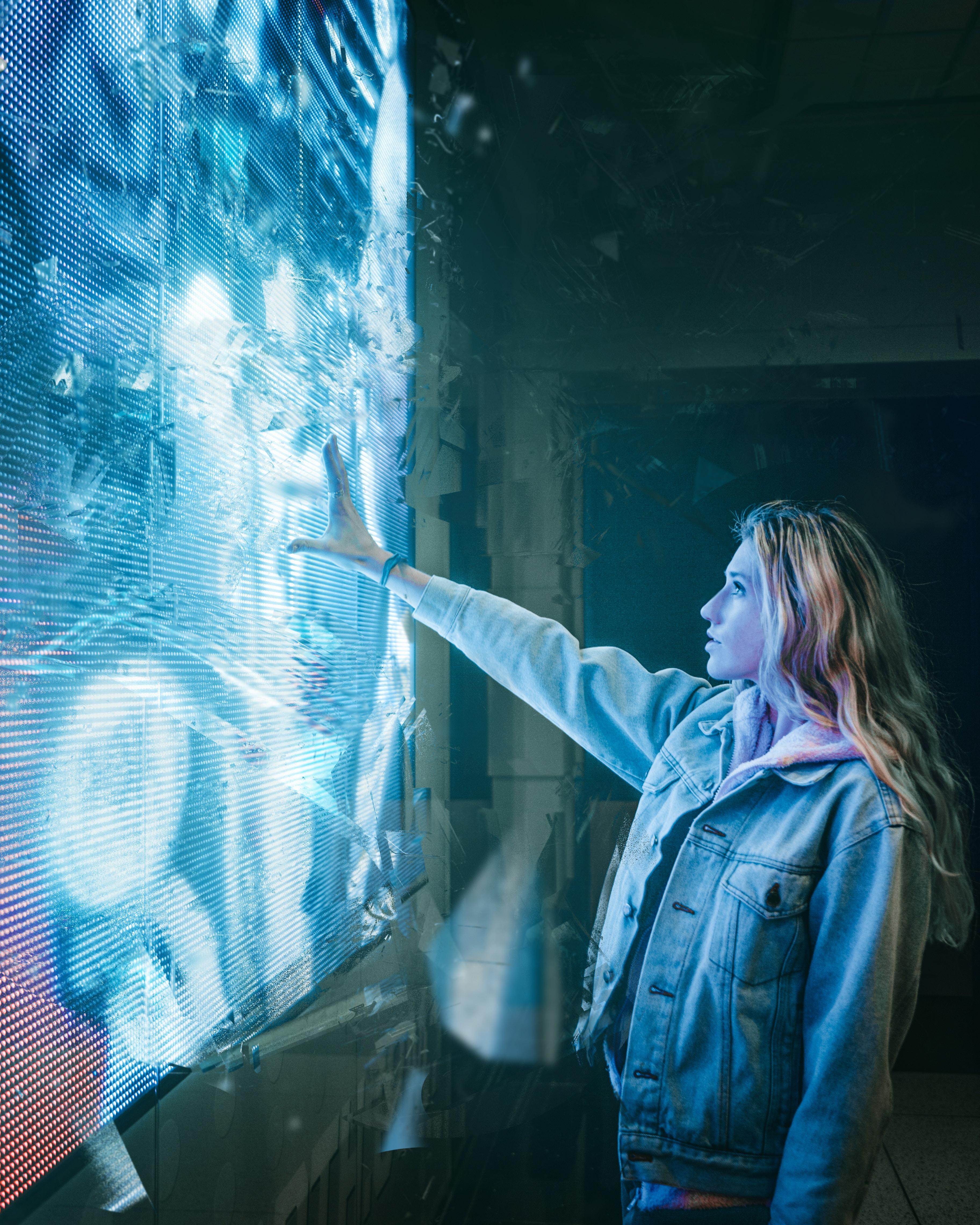 A lady touching a high tech screen.